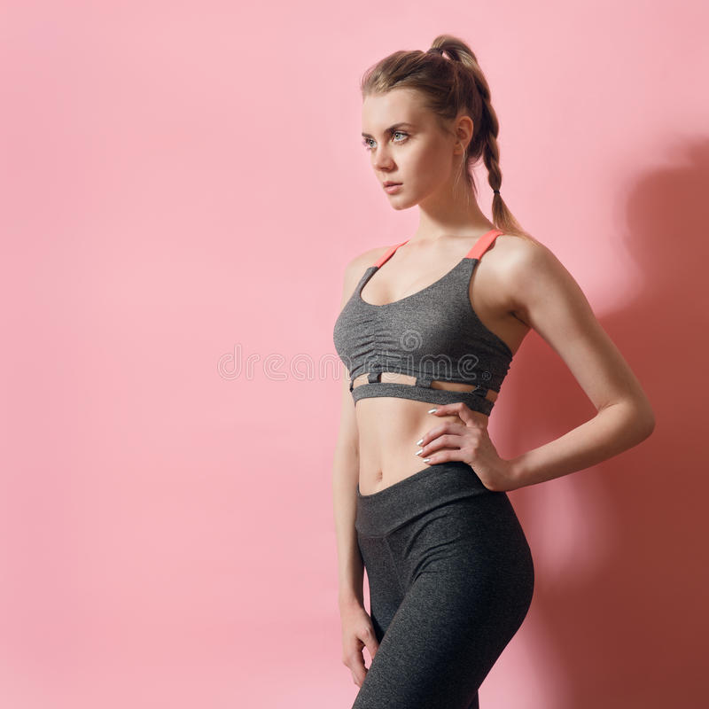 Fitness model woman focused on sport goals. Beautiful woman wearing sport clothes posing royalty free stock images