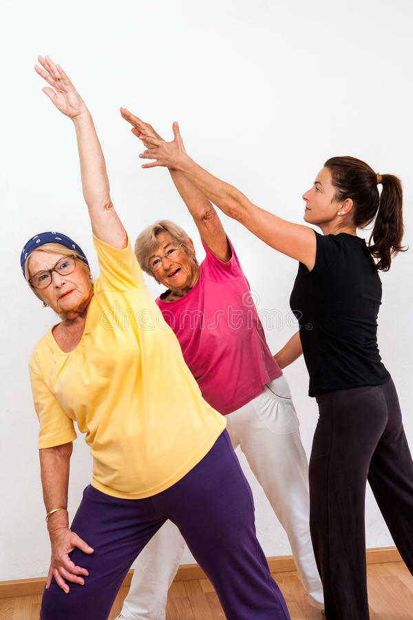 Fitness monitor helping senior ladies in class. Female aerobic instructor helping senior ladies in fitness session royalty free stock image