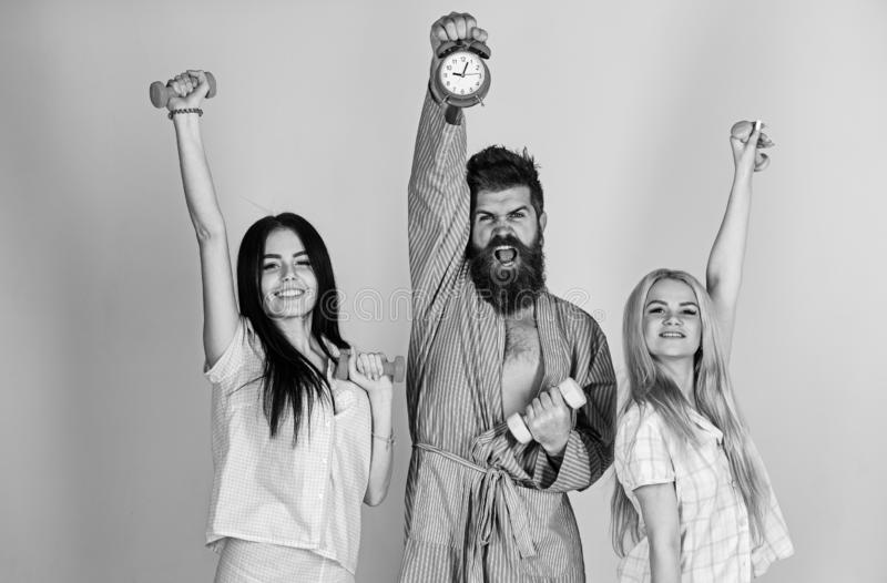 Fitness morning concept. Cheerful friends with dumbbells in domestic clothes, grey background. Bearded man holds alarm. Fitness morning concept. Cheerful friends royalty free stock image