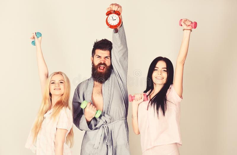Fitness morning concept. Cheerful friends with dumbbells in domestic clothes, grey background. Bearded man holds alarm. Fitness morning concept. Cheerful friends royalty free stock photos
