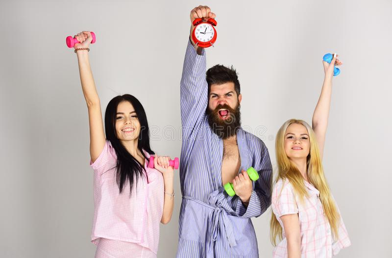 Fitness morning concept. Cheerful friends with dumbbells in domestic clothes, grey background. Bearded man holds alarm. Fitness morning concept. Cheerful friends royalty free stock photography