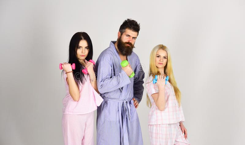 Fitness morning concept. Company of friends with dumbbells in domestic clothes, on grey background. Trainer, macho with. Attractive girls do morning exercises stock photos
