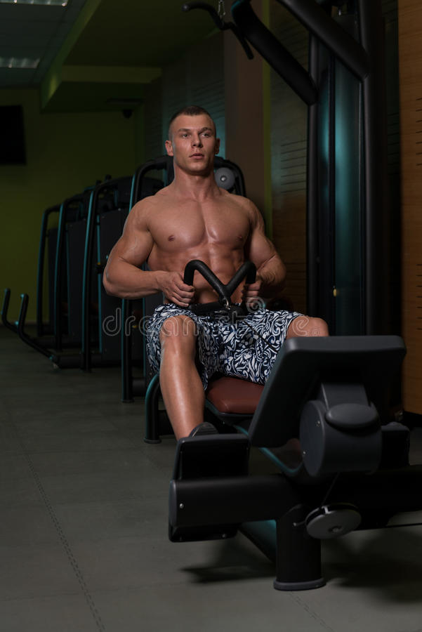 Fitness Muscle Man Exercise Back On Machine. Muscular Athletic Bodybuilder Fitness Model Doing Heavy Weight Exercise For Back On Machine stock photos