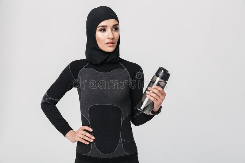 Fitness muslim isolated over white wall background drinking water. Image of young woman fitness muslim isolated over white wall background drinking water royalty free stock photo