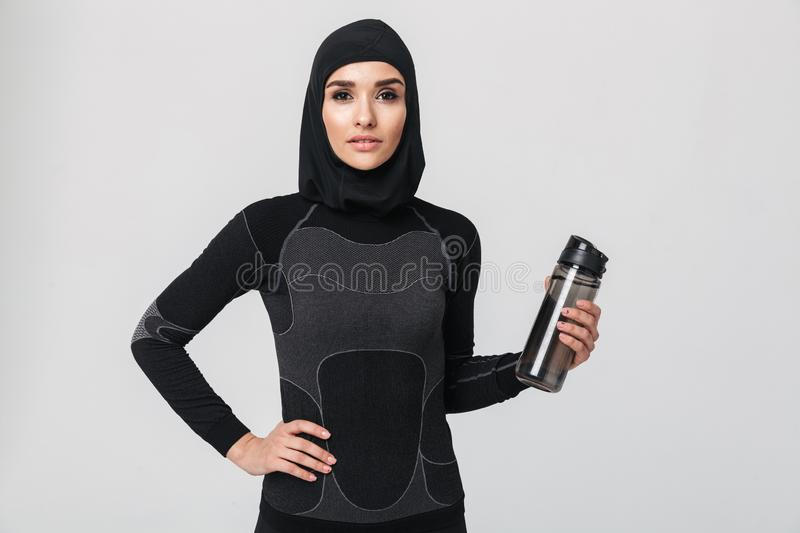 Fitness muslim isolated over white wall background drinking water. Image of young woman fitness muslim isolated over white wall background drinking water stock photos