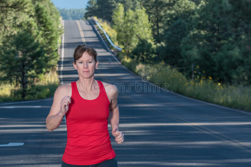 Fitness Over Forty Woman Running. Female over forty running in countryside stock photos