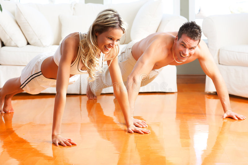 Fitness people. Young man and woman woman doing exercise in the sunny room