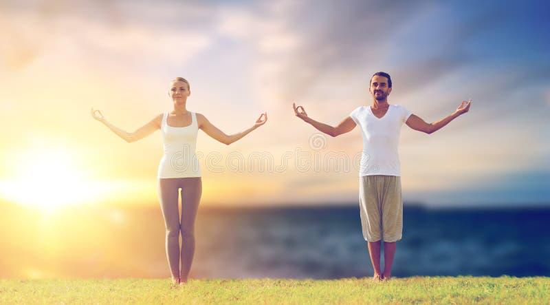Couple making yoga exercises outdoors royalty free stock photos