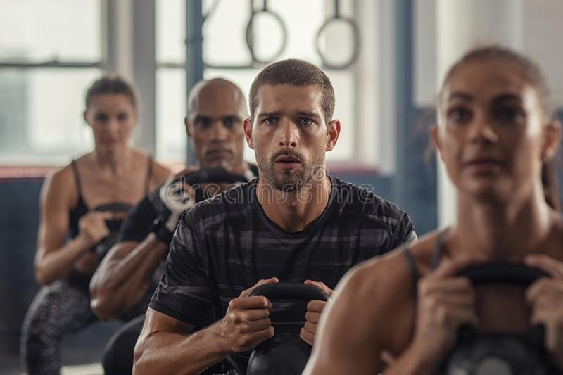 Fitness people exercising using kettle bell. Portrait of fitness men lifting kettle bell with young women in fitness center. Active guy with group of people in stock photos
