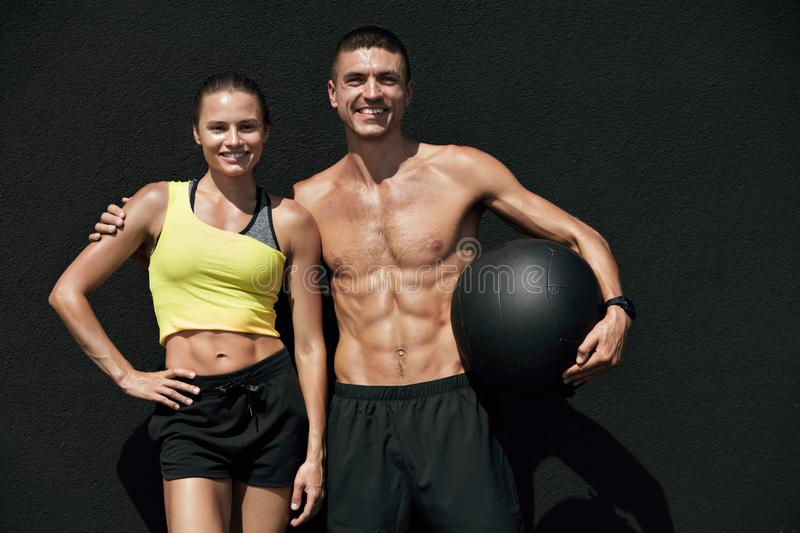 Fitness people in sport clothes after workout with med ball. Outdoors. Happy smiling fit couple after successful exercising on gray background royalty free stock images