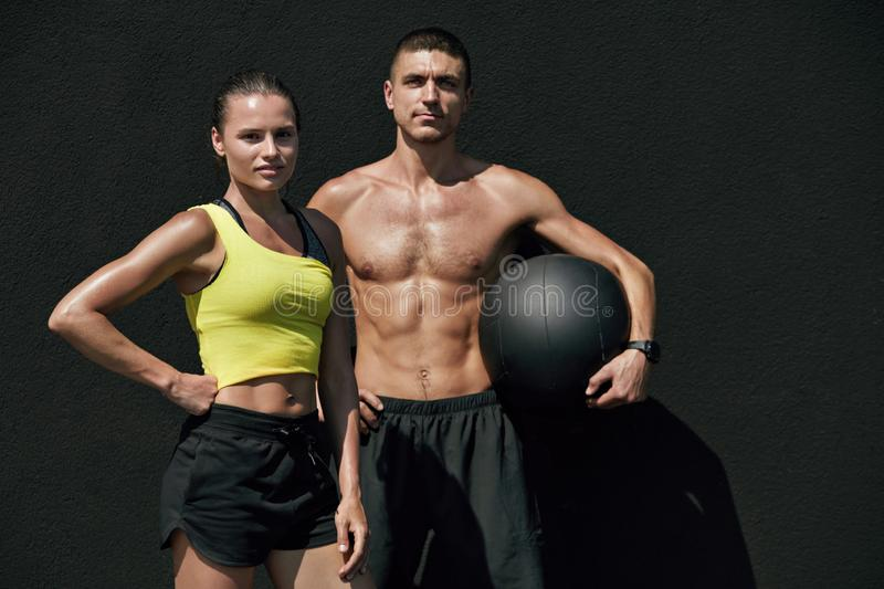 Fitness people in sport clothes after workout with med ball. Outdoors. Happy smiling fit couple after successful exercising on gray background stock image