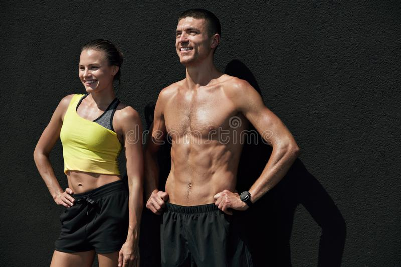 Fitness people in sport clothes after workout with med ball. Outdoors. Happy smiling fit couple after successful exercising on gray background stock photography