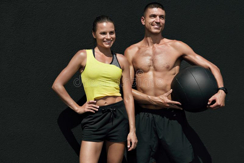 Fitness people in sport clothes after workout with med ball. Outdoors. Happy smiling fit couple after successful exercising on gray background royalty free stock photography