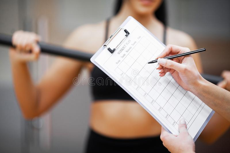 Fitness plan. Sports trainer amounts to workout plan close-up stock image