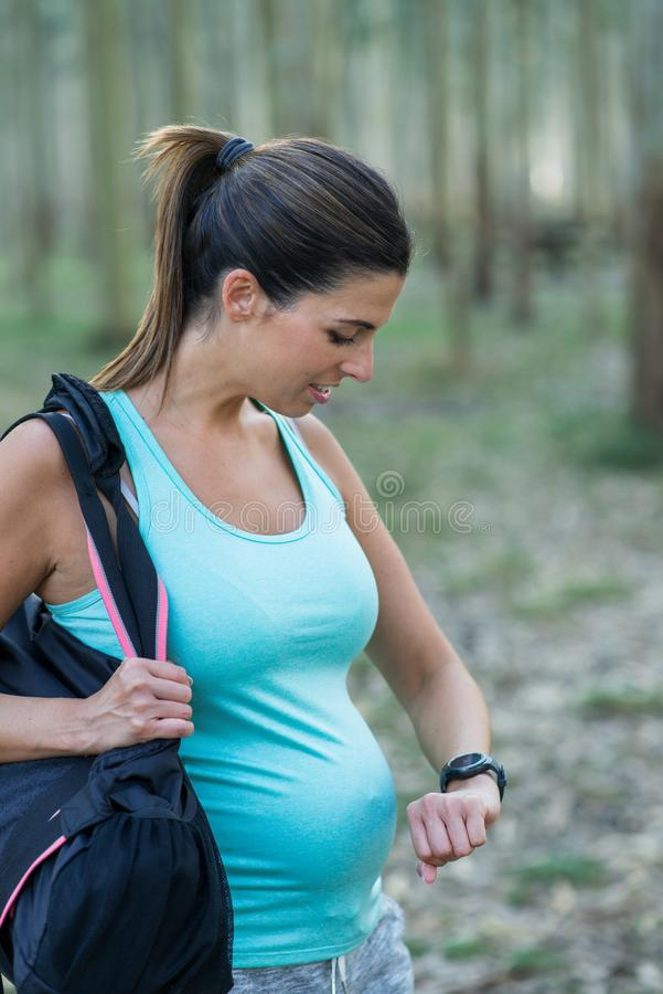 Fitness pregnant woman checking contraction duration stock images