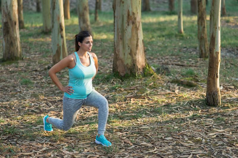 Pregnant fitness woman doing lunges outdoor royalty free stock photo