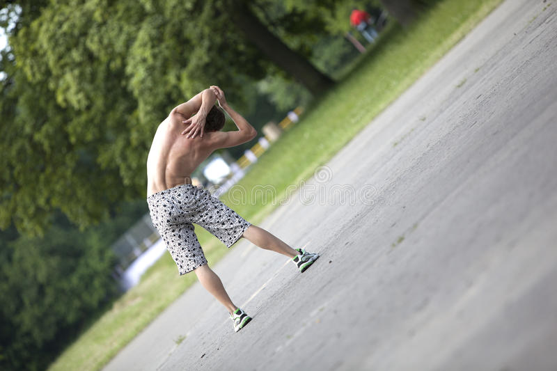fitness program - man stretching stock images