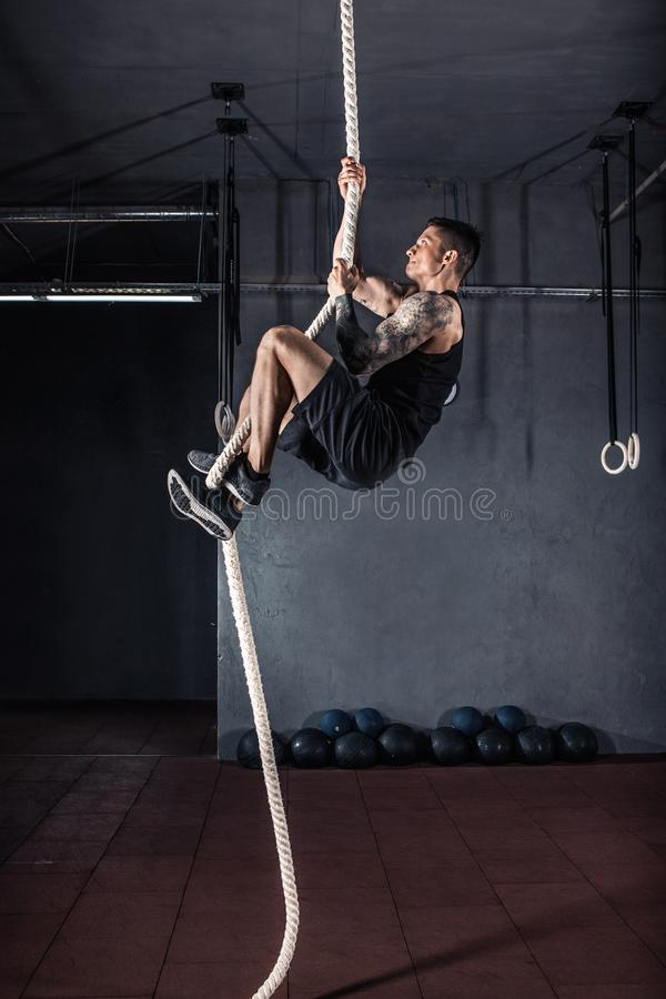 Athlete doing rope climb at gym stock photo