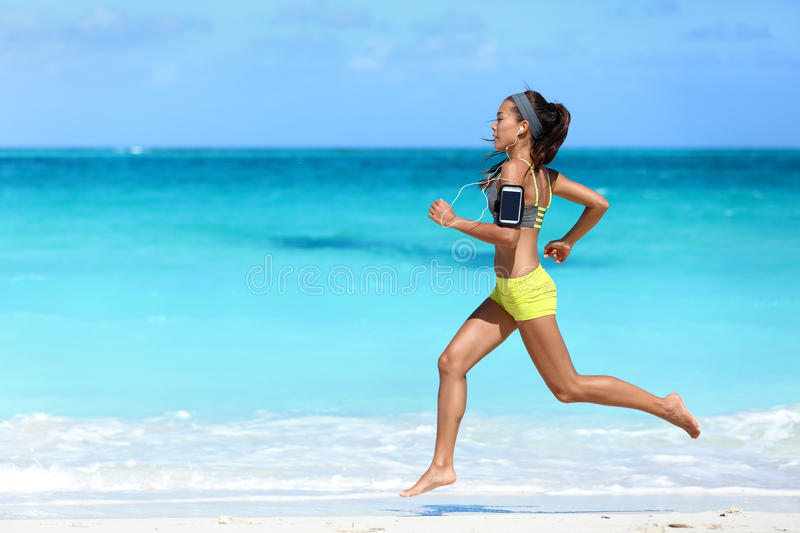 Fitness runner woman beach running listening to music with phone sport armband stock images