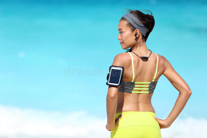 Fitness runner woman with fit back wearing phone armband and wireless headphones royalty free stock image