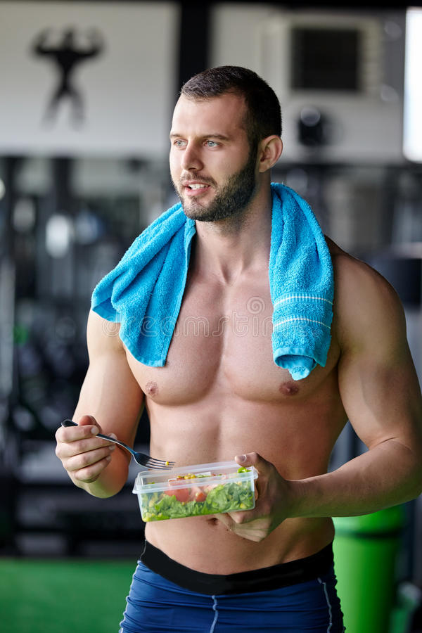Fitness salad. Fitness man holding a bowl of fresh salad stock photo