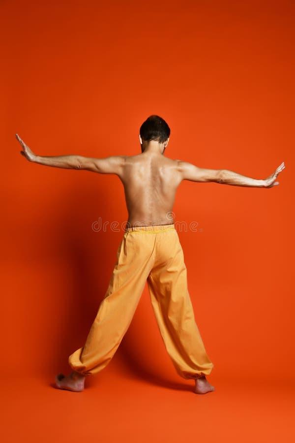 Fitness senior man doing exercise yoga asana leg isolated on a orange background royalty free stock photo