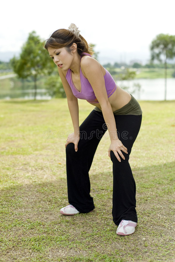 Fitness series exhaustion. An asian female is holding her knees trying to catch a breath due to exhaustion royalty free stock images
