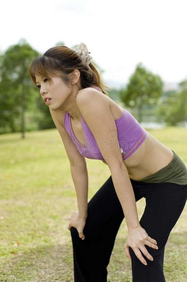 Fitness series exhaustion. An asian female is holding her knees trying to catch a breath due to exhaustion royalty free stock image