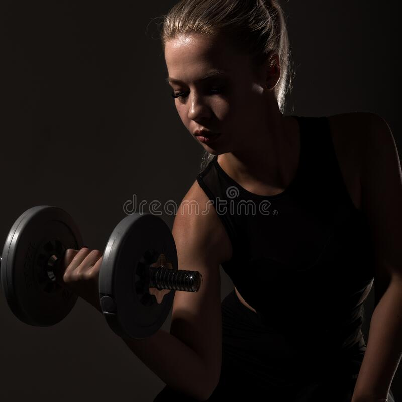 Fitness sexy girl with dumbbells on a dark background. Athlete doing exercises in the gym stock photography