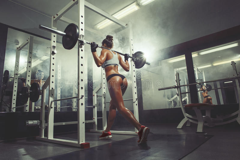 Fitness girl in the gym doing squat on smoke background. Bodybuilder woman in the gym doing squat with barbell on smoke background royalty free stock photography