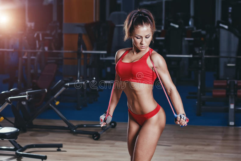 Fitness girl with healthy sporty figure with skipping rope in gym royalty free stock images