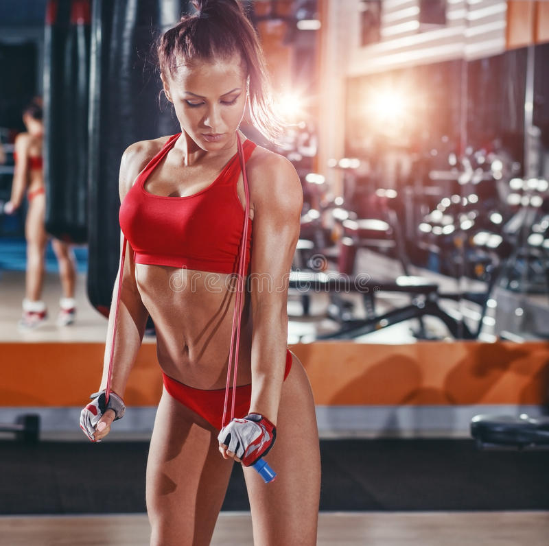 Fitness girl with healthy sporty figure with skipping rope in gym royalty free stock photography
