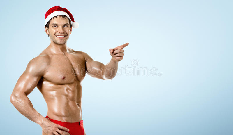 Fitness Santa Claus , show index finger and smile, on blue. Background royalty free stock photo