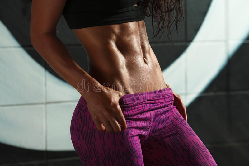 Fitness woman showing abs and flat belly. Beautiful muscular girl, shaped abdominal, slim waist stock image