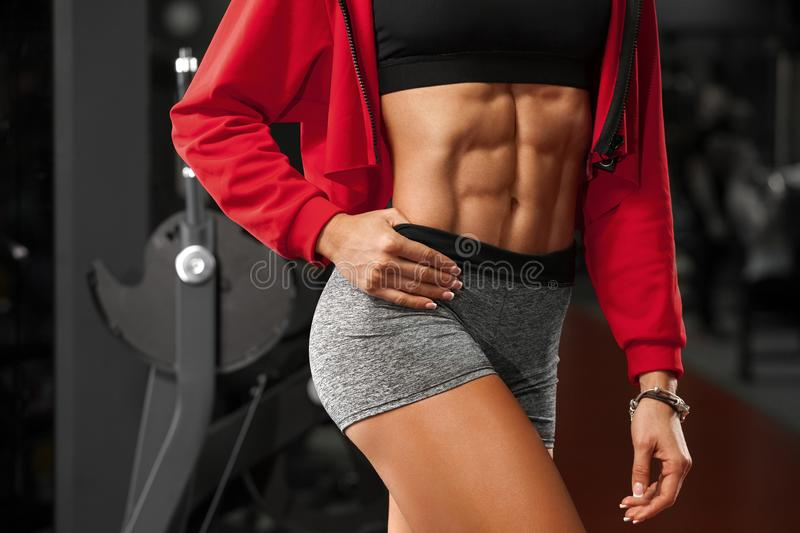 Fitness woman showing abs and flat belly in gym. Beautiful athletic girl, shaped abdominal, slim waist royalty free stock image