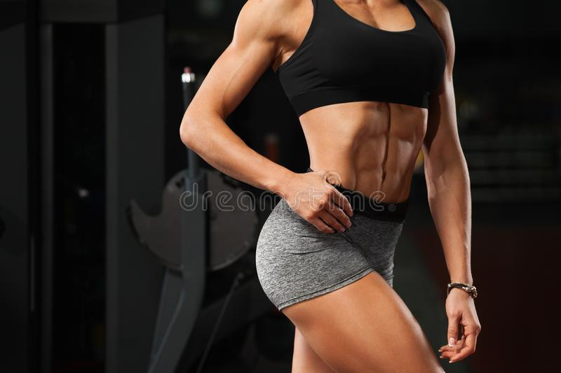 Fitness woman showing abs and flat belly in gym. Beautiful athletic girl, shaped abdominal, slim waist stock photo
