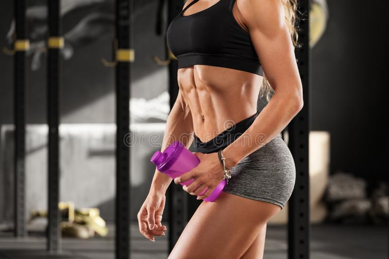 Fitness woman showing abs and flat belly in gym. Beautiful muscular girl, shaped abdominal, slim waist stock images