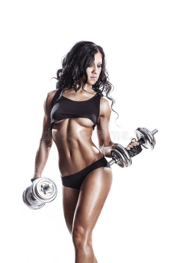 Fitness young woman in sport wear with perfect fitness body training with dumbbells. Young muscled fitness brunette girl back posing isolated over white stock image
