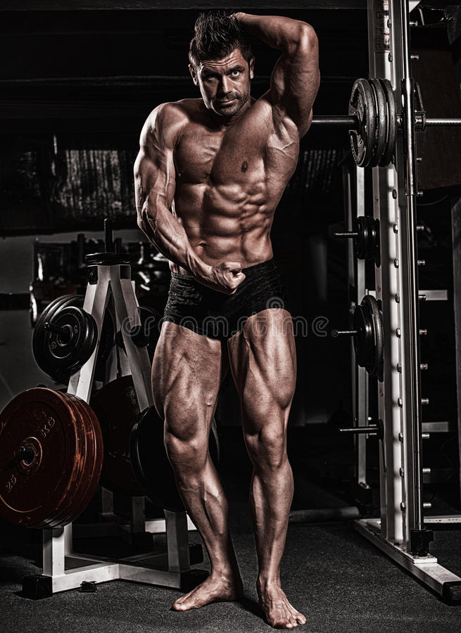 Fitness shaped muscle man posing on dark gym royalty free stock photography