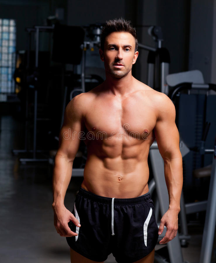 Fitness shaped muscle man posing on gym royalty free stock photos