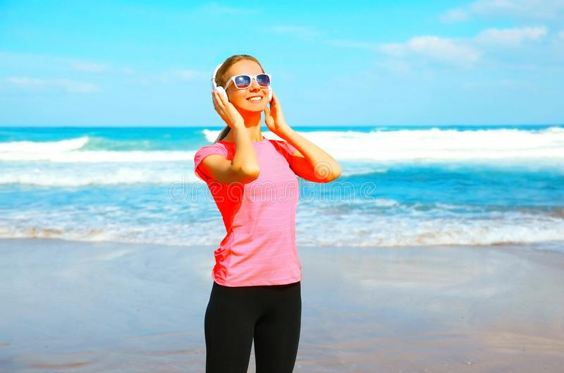 Fitness smiling woman listens to music in wireless headphones on the beach. On a summer day stock images
