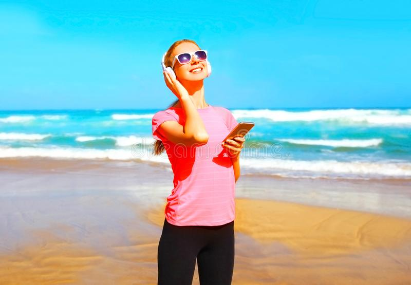 Fitness smiling woman listens to music in wireless headphones. Fitness smiling woman listens to music in a wireless headphones with smartphone on the beach stock photo