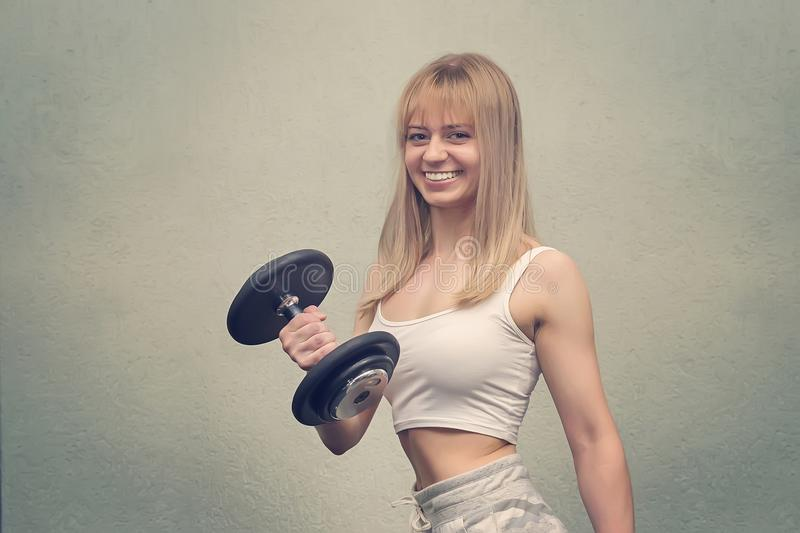 Fitness. Sport concept. Workout. Blonde girl holds pink dumbbells. Fitness girl. Healthy lifestyle. Training. Workout. Smiling hap royalty free stock images