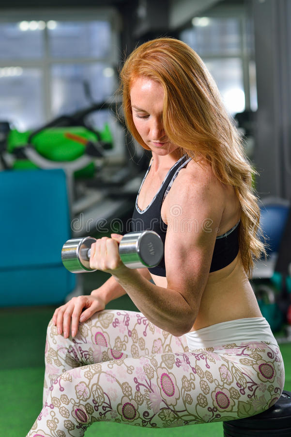 Fitness, sport, die levensstijl uitoefenen - Aantrekkelijke jonge vrouw die gewichtheffenoefeningen op bicepsen doen bij gymnasti stock afbeeldingen