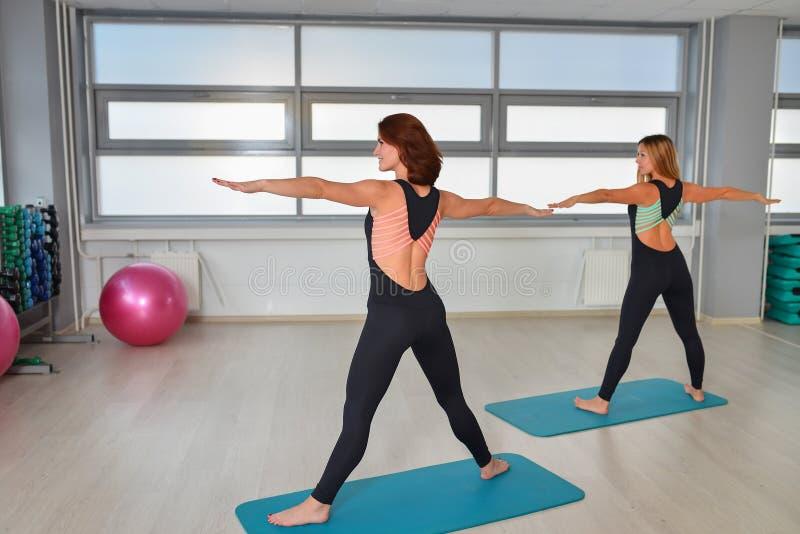 Fitness, sport, die levensstijl uitoefenen - de Gelukkige vrouwen dragen in bodysuits die oefeningen doen bij gymnastiek royalty-vrije stock fotografie