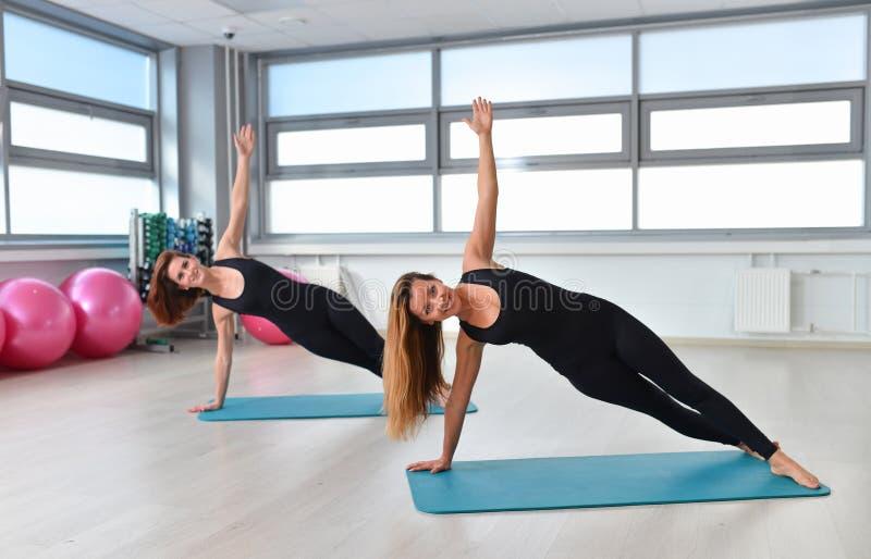 Fitness, sport, die levensstijl uitoefenen - Twee jonge vrouwen die de zijplank van yogaasana doen Vasisthasana stock afbeeldingen