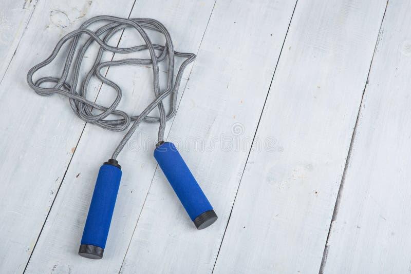 Fitness/sport en gezond levensstijlconcept - het Springen/touwtjespringen met blauwe handvatten stock afbeeldingen