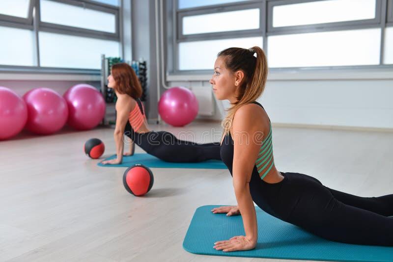 Fitness, sport, exercising lifestyle - female group doing warm up yoga pose at gym.  stock photography
