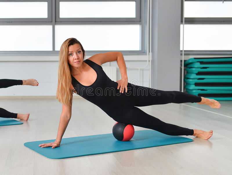 Fitness, sport, exercising lifestyle - fit woman in bodysuit doing exercises with medicine ball at gym.  stock photos