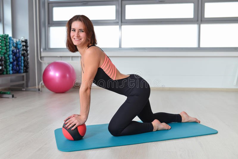 Fitness, sport, exercising lifestyle - fit woman in bodysuit posing on mat with medicine ball at gym.  stock photos